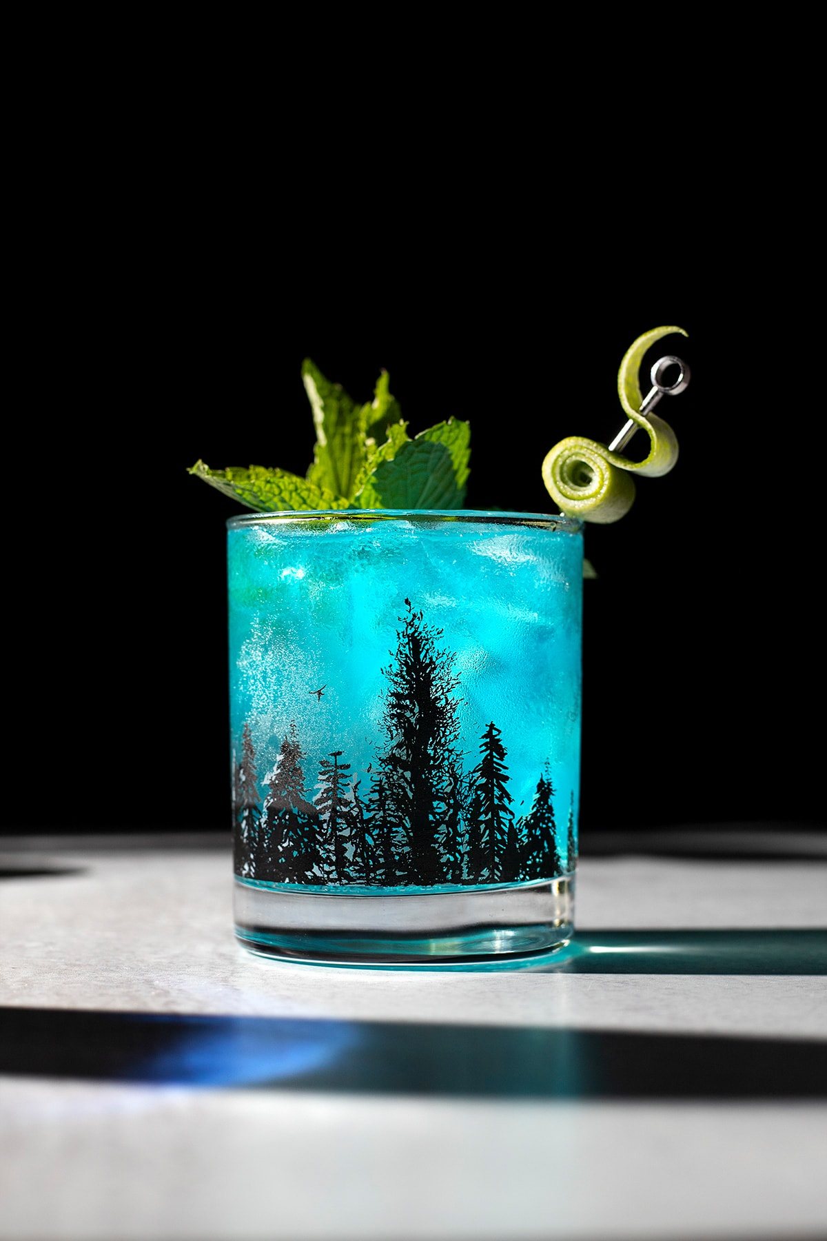 a bright blue drink in a rocks glass with black trees on it.