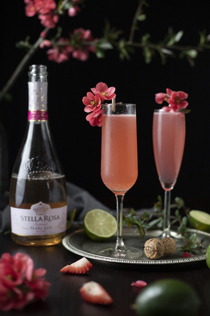 two finished pink cocktails in champagne flutes garnished quince flowers