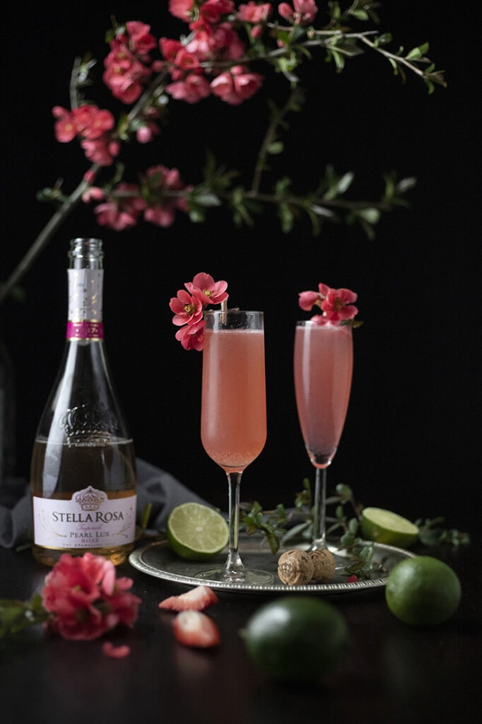 two pink cocktails in champagne flutes next to a bottle of Stella Rosa