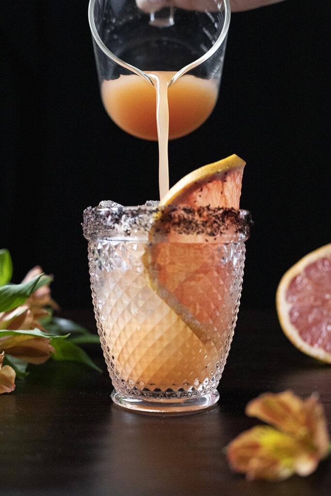 pouring grapefruit juice into a double rocks glass