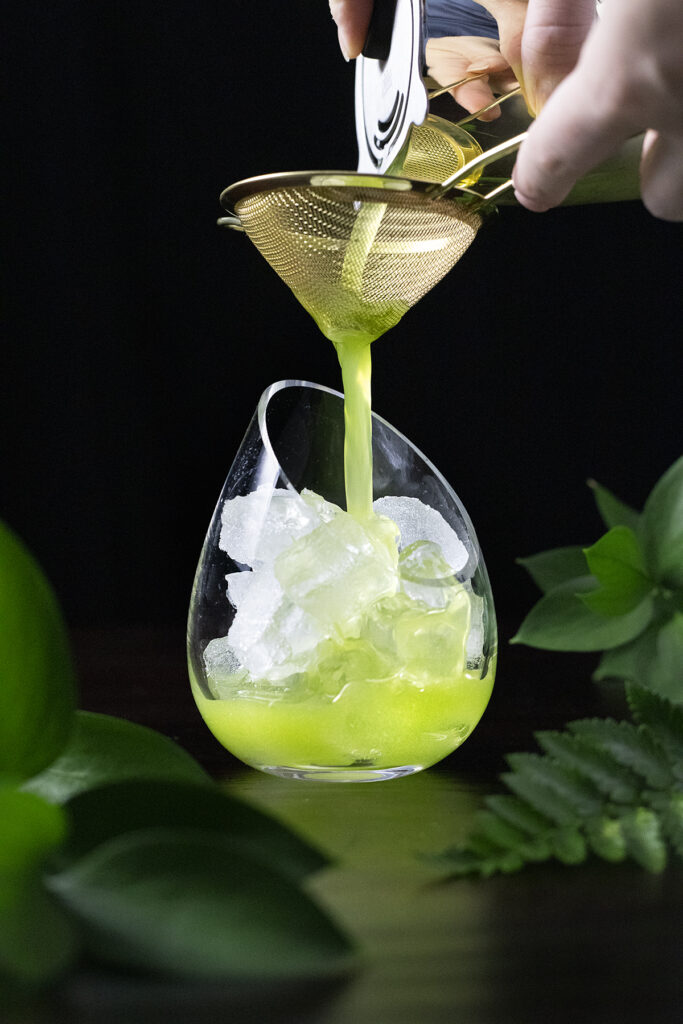pouring a green drink through a fine mesh strainer.