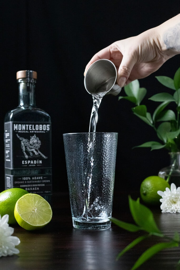 pouring an ounce of mezcal into a mixing glass.