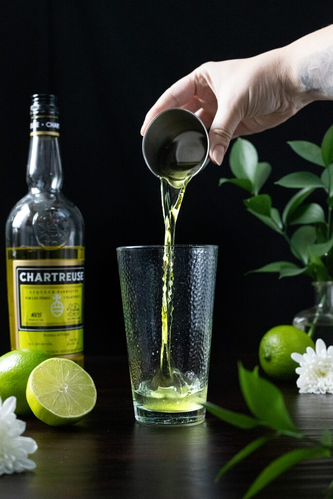 pouring an ounce of yellow Chartreuse into a mixing glass.