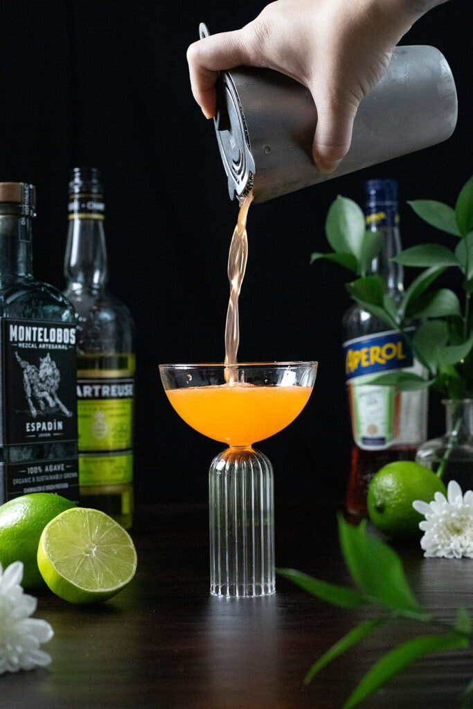 straining an orange cocktail into a coupe glass.