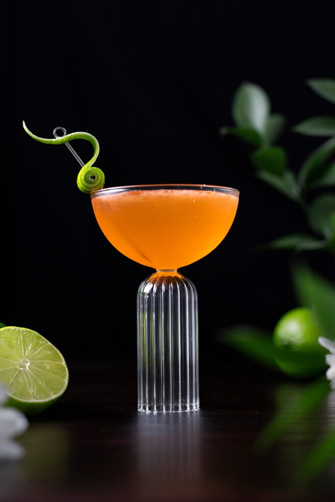 orange cocktail in a coupe glass with a fancy lime peel garnish.