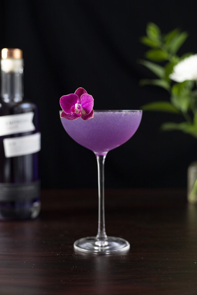 a purple cocktail in a coupe glass with a pink orchid garnish.