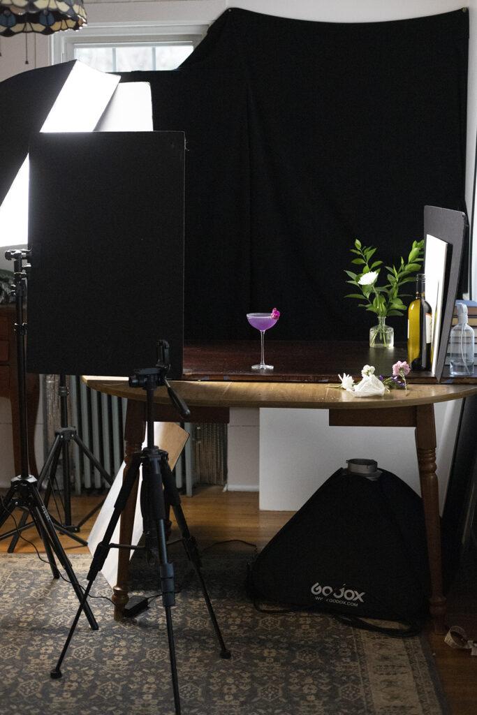 a photo studio setup with lighting and black backdrop.