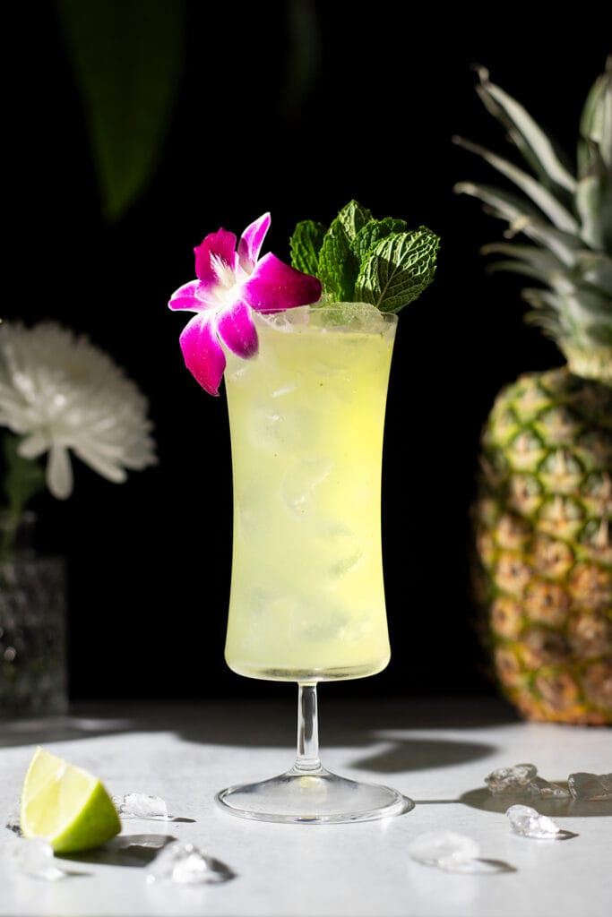 tropical cocktail in a hurricane glass with an orchid.