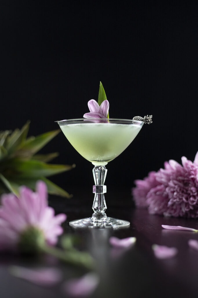 a pale green cocktail with pale purple flowers