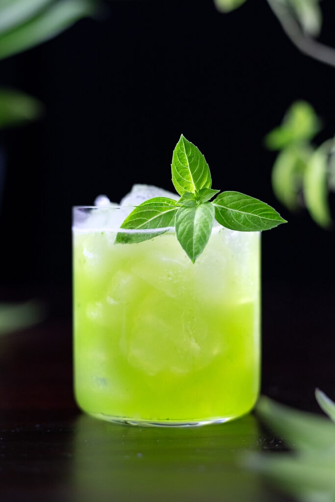 green basil smash in a rocks glass with basil leaves.