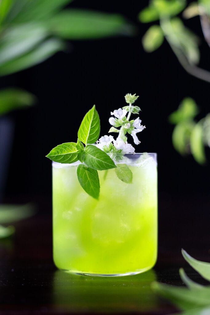 green basil smash in a rocks glass with basil leaves and a basil flower.