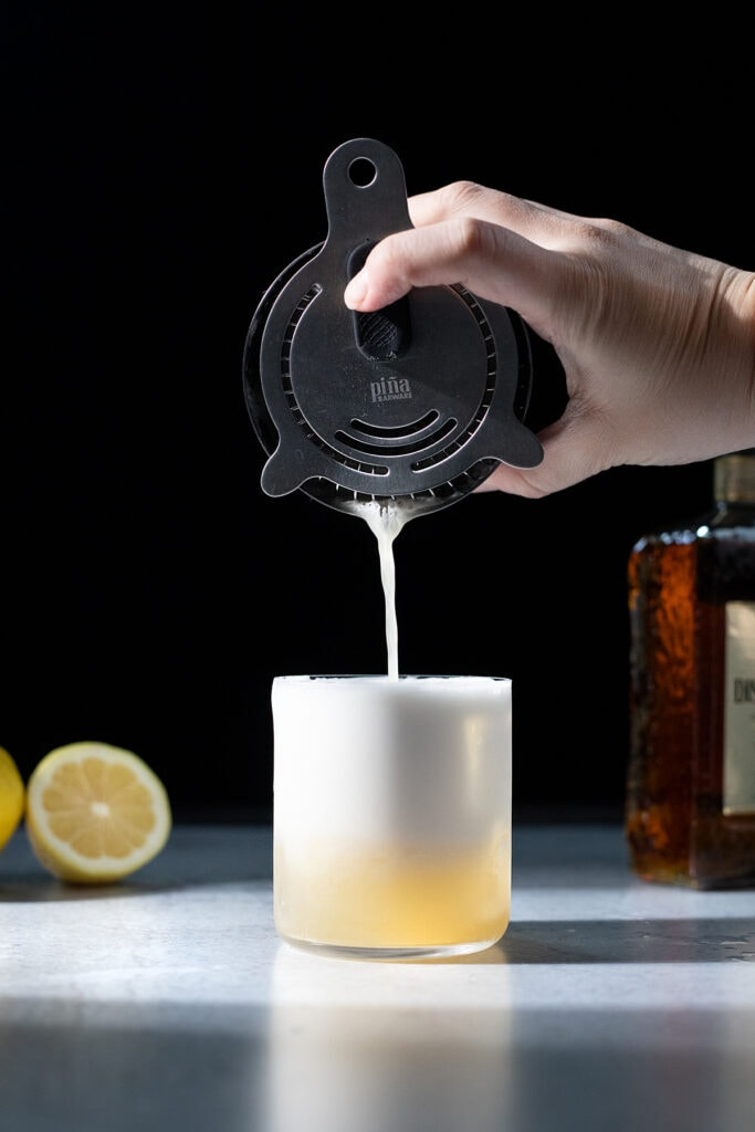 pouring a foamy cocktail into a rocks glass filled with ice.