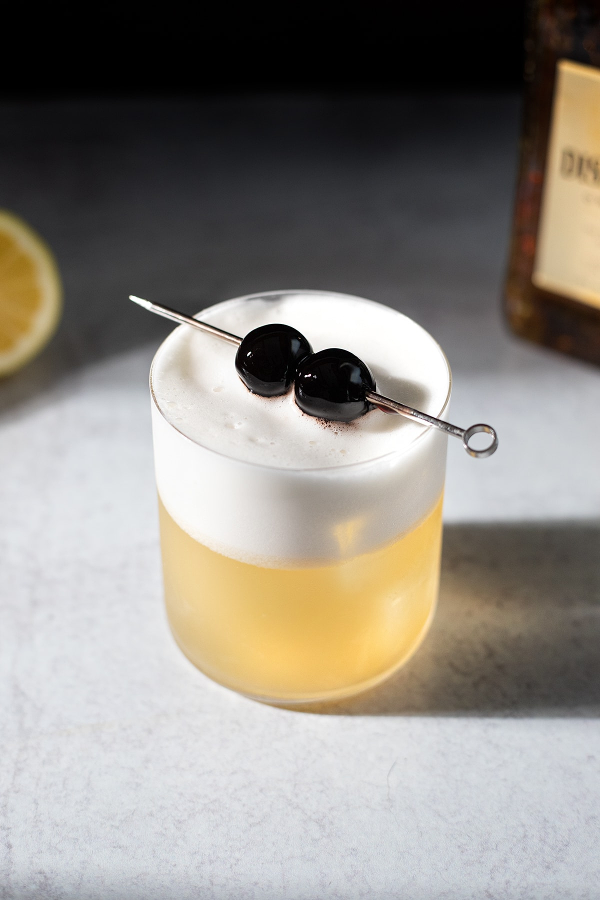a golden colored cocktail with thick white foam and two cherries.