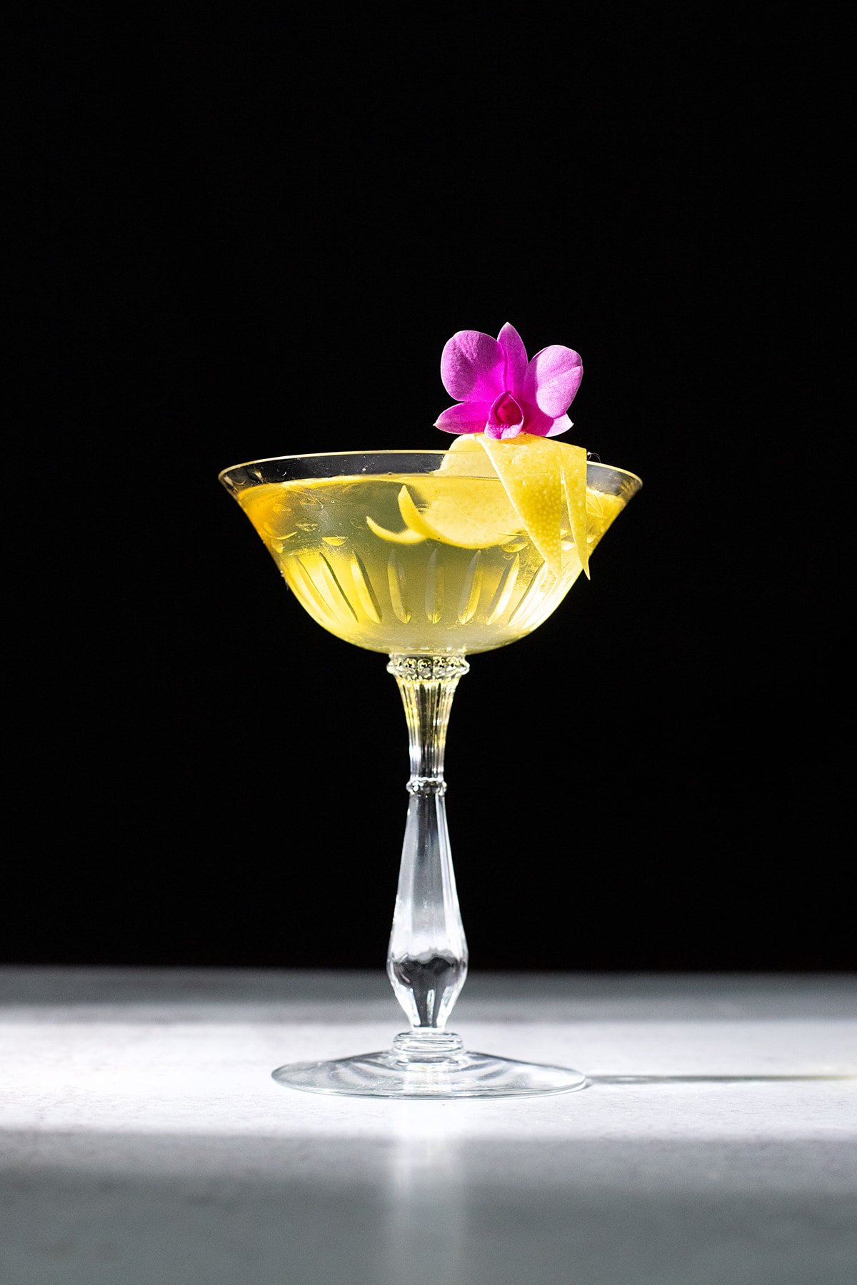 bright yellow cocktail in a coupe glass.