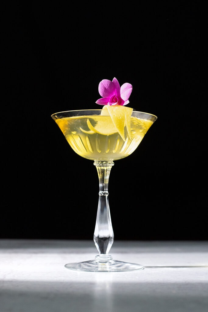 bright yellow cocktail in a coupe glass with pink flower.