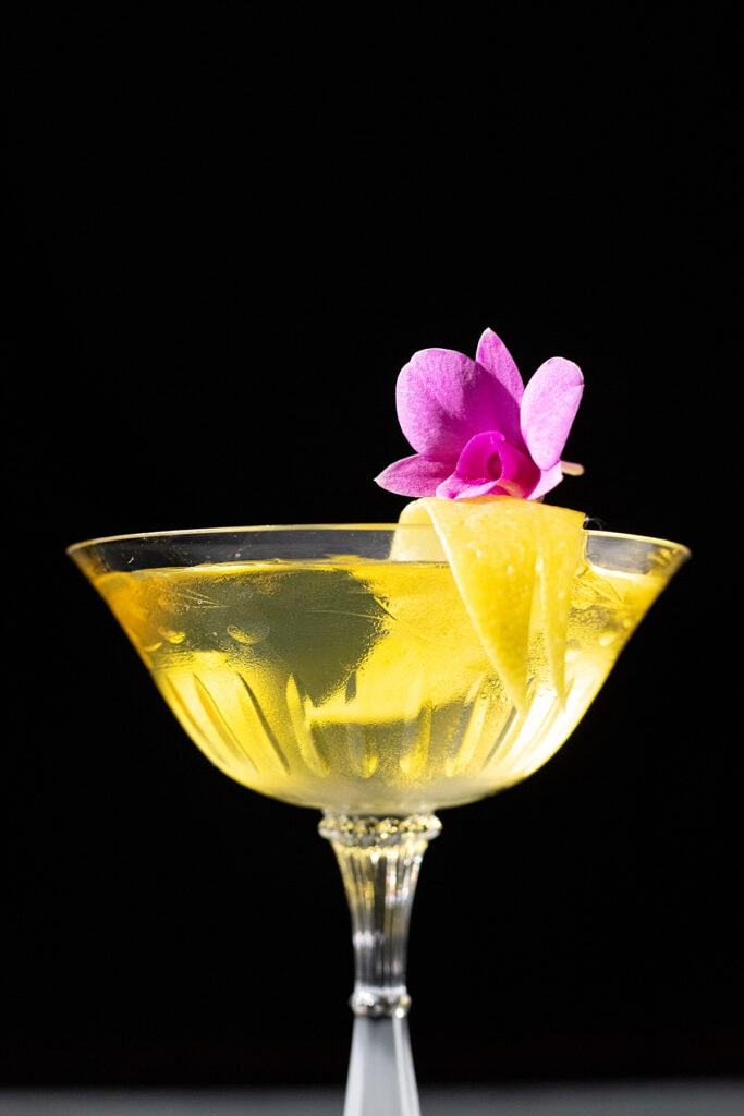 yellow cocktail with a lemon peel and pink orchid.