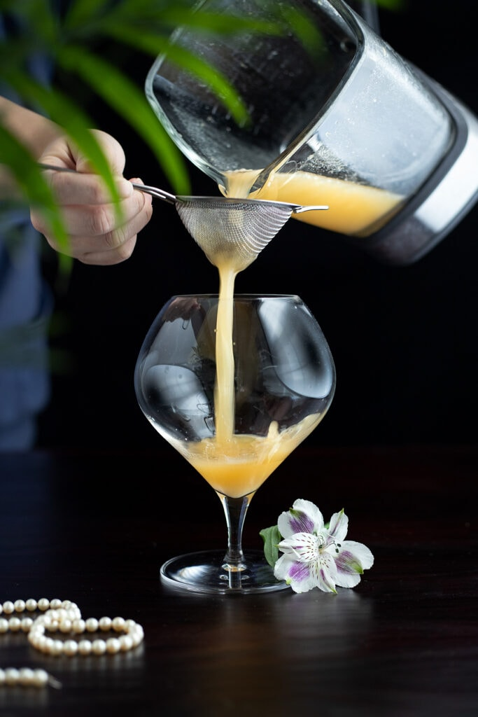 straining the Pearl Diver cocktail into a glass.