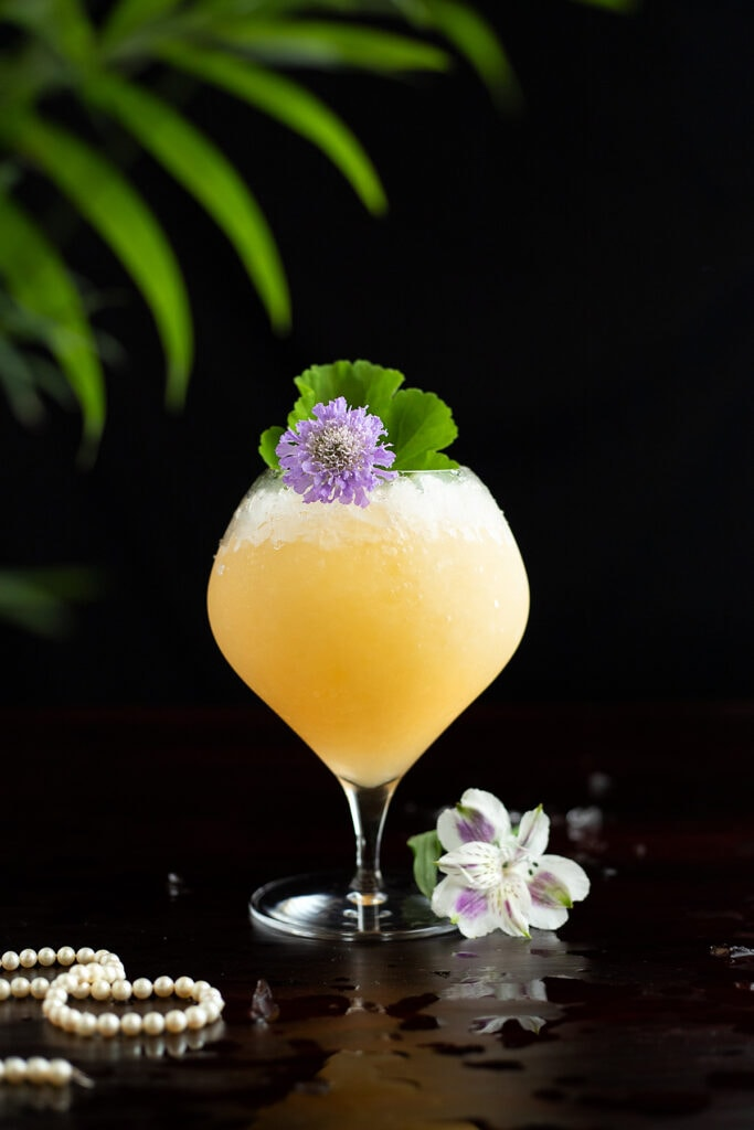 a pearl diver cocktail with an edible flower
