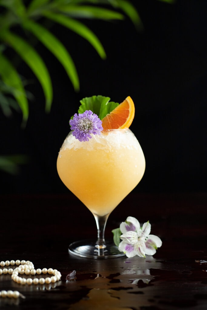 a tropical drink with a strand of pearls.