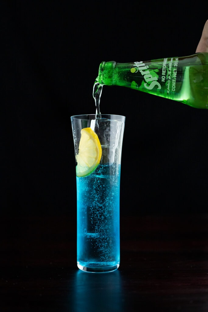 topping a blue cocktail with Sprite.