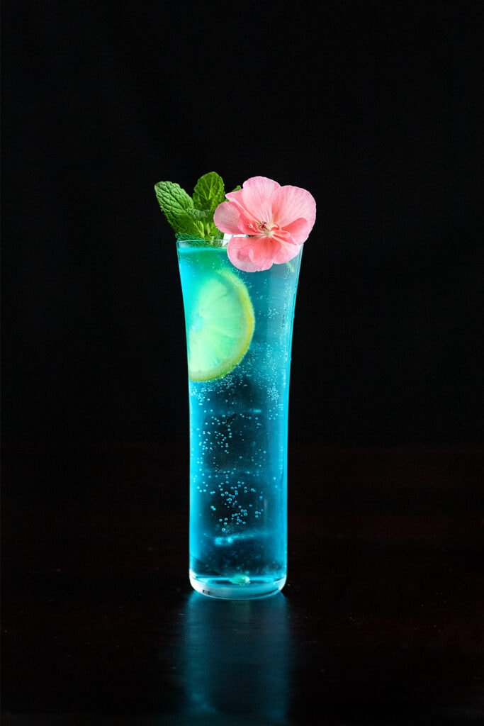 tall blue cocktail with mint and a pink flower.