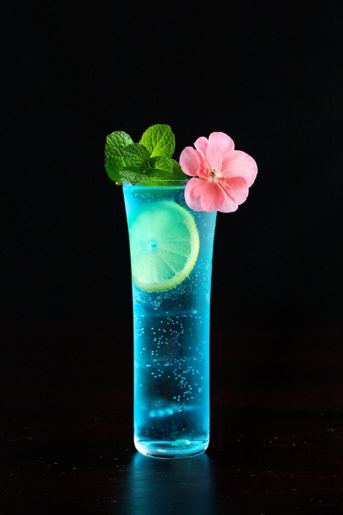 Blue AMF cocktail with a lemon wheel, mint sprig, and pink flower.