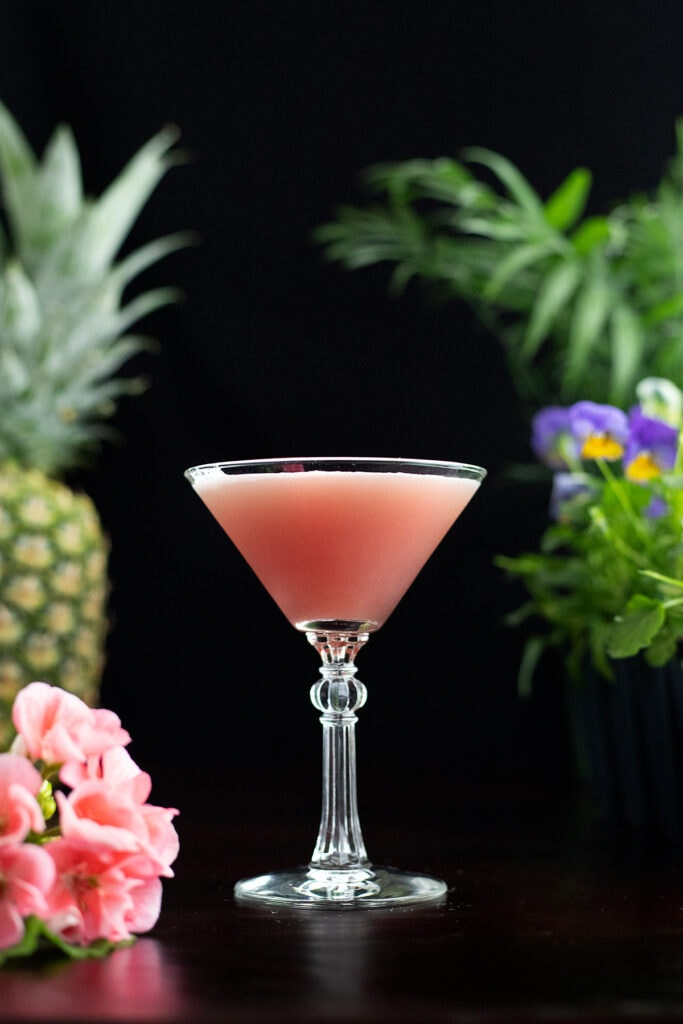 A pink Mary Pickford cocktail with flowers