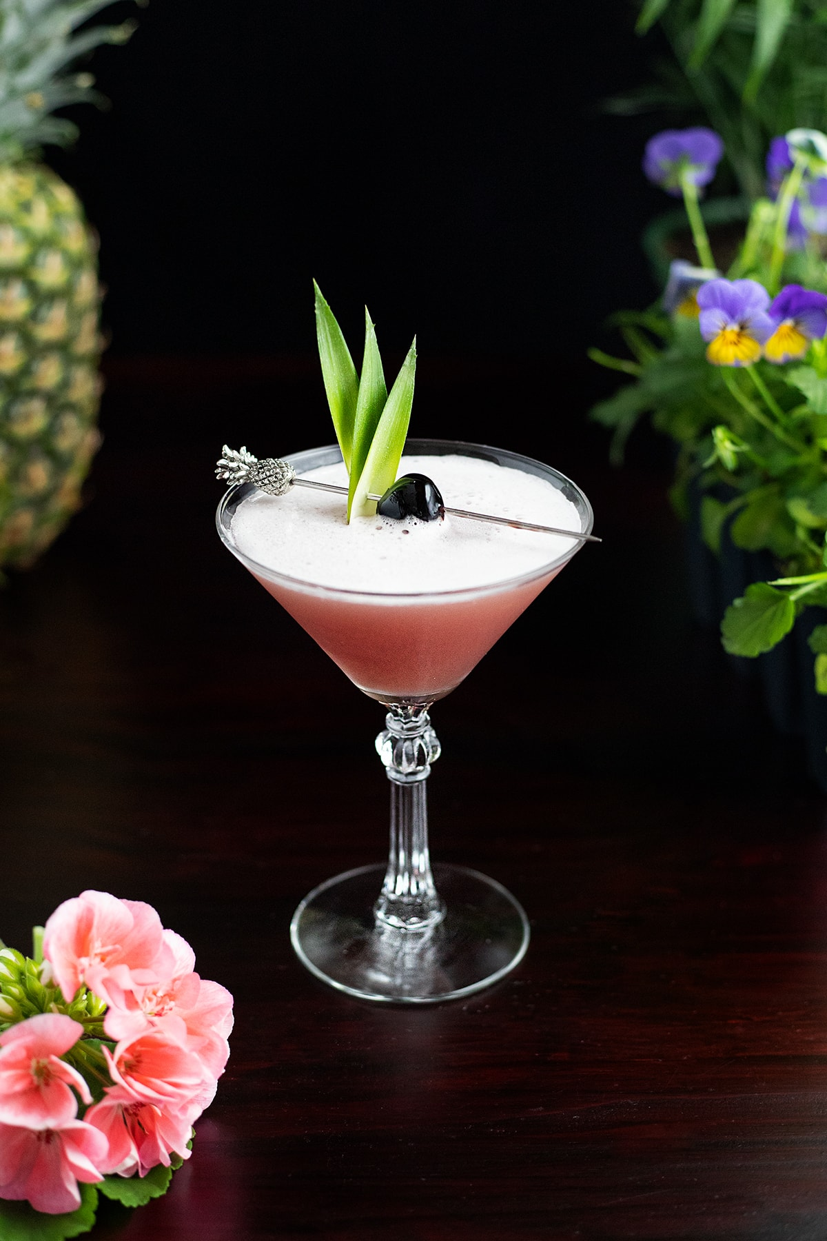 pink tropical cocktail in a martini glass with pineapple leaves.