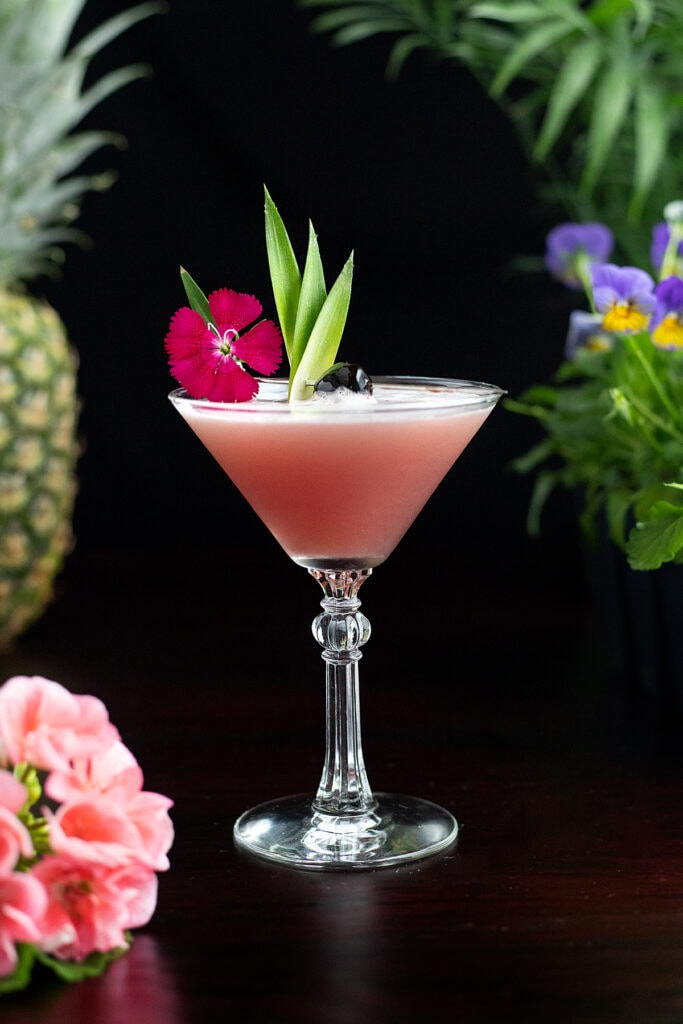 Mary Pickford cocktail garnished with a pink flower, cherry, and pineapple leaves.