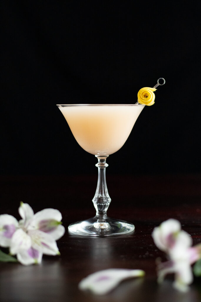 Army and Navy cocktail garnished with a lemon twist on a cocktail pick.