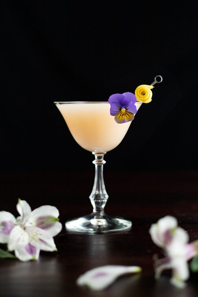 a pale creamy cocktail garnished with edible flowers.