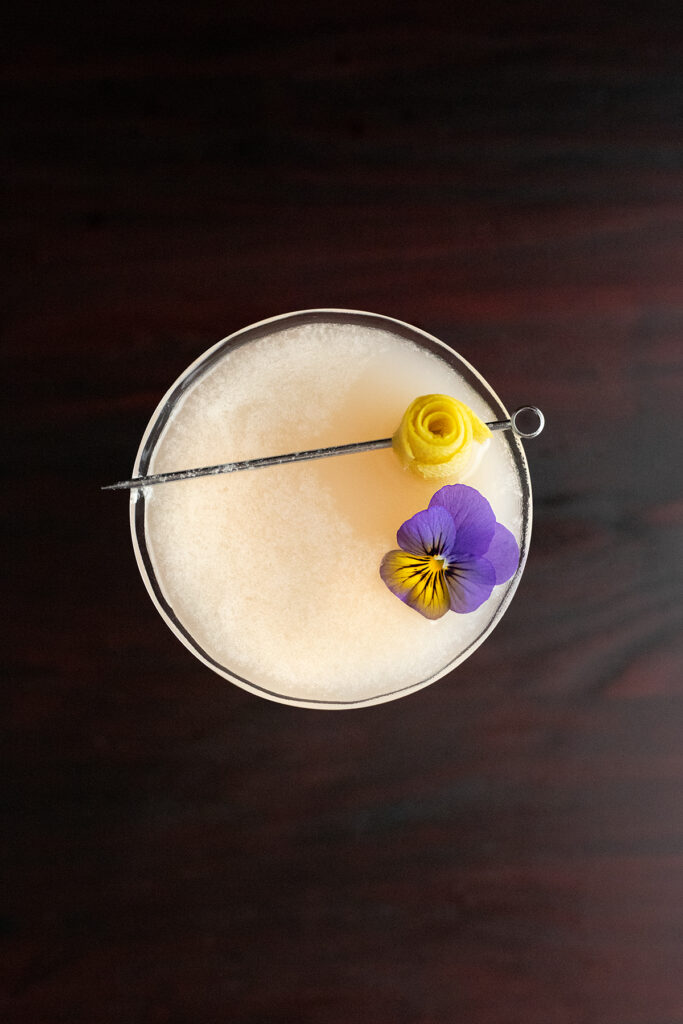 overhead view of edible viola flower floating in a cocktail.