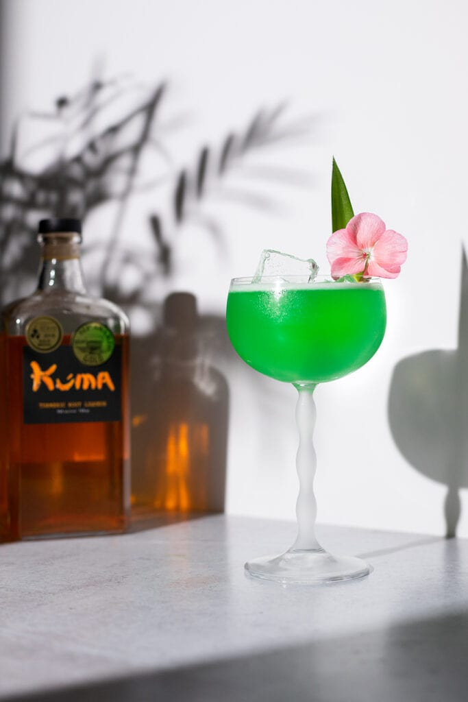 a green margarita next to a bottle of Kuma Turmeric Liqueur.