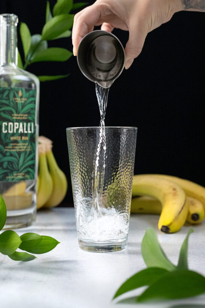 pouring white rum from a measuring cup into a cocktail shaker.