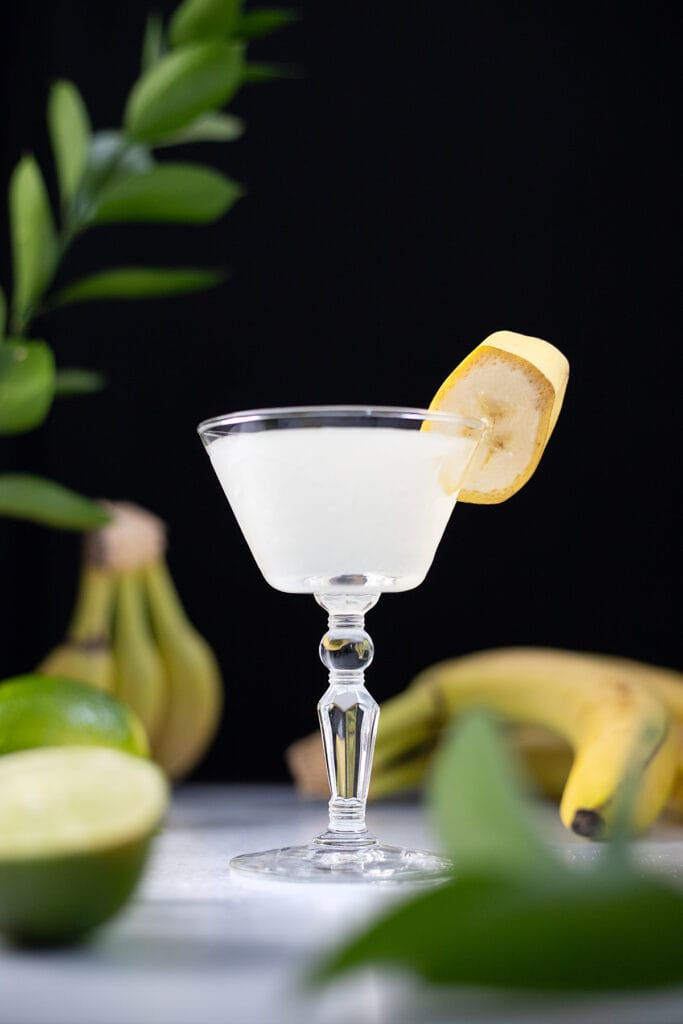 a white cocktail with a banana slice next to bananas and limes.