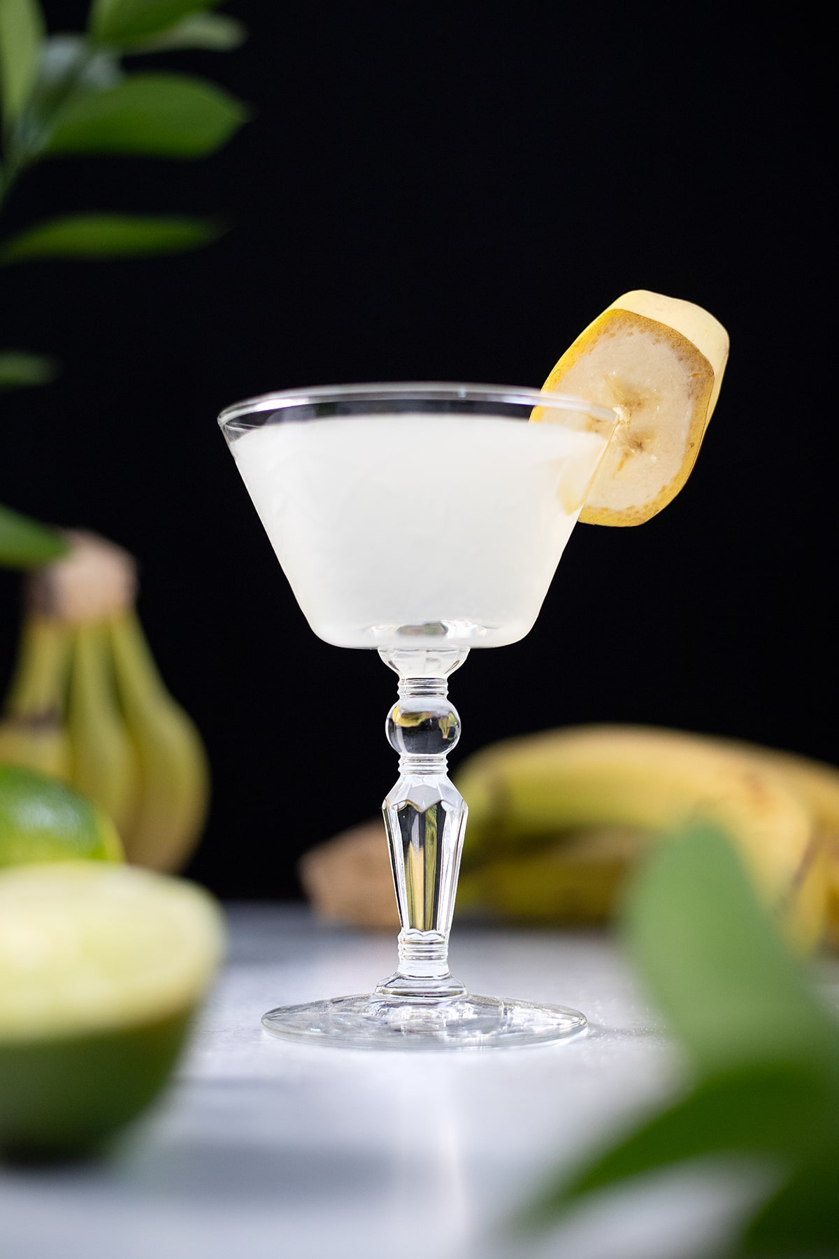 a white cocktail in a vintage glass with a banana slice on the rim.