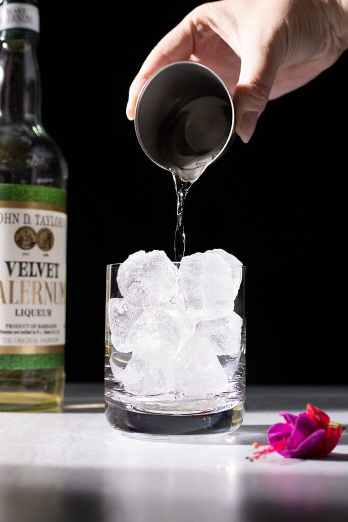 pouring falernum over ice.