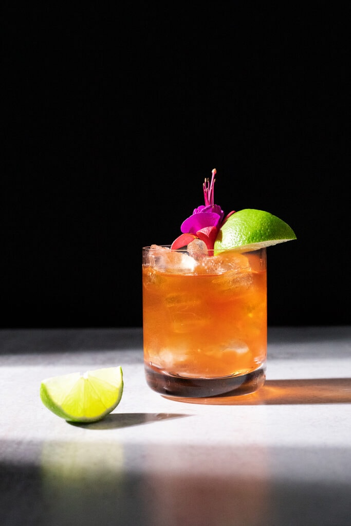 corn 'n oil cocktail with lime wedges.