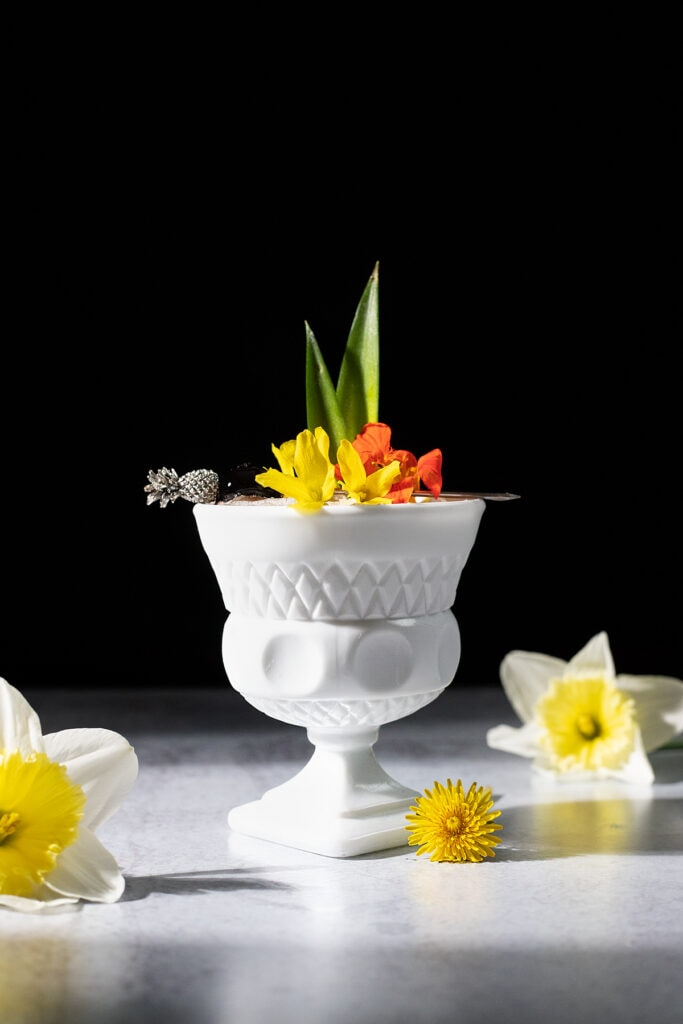 tropical cocktail in a white glass cup with flowers and pineapple leaves.