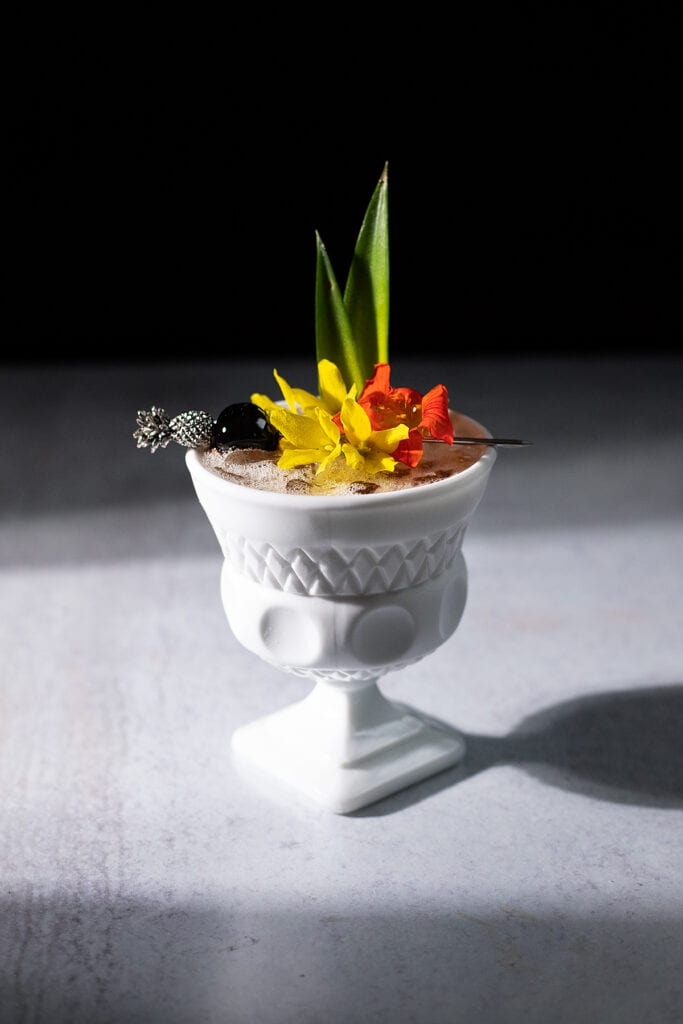 tropical drink in a white glass cup with flowers.