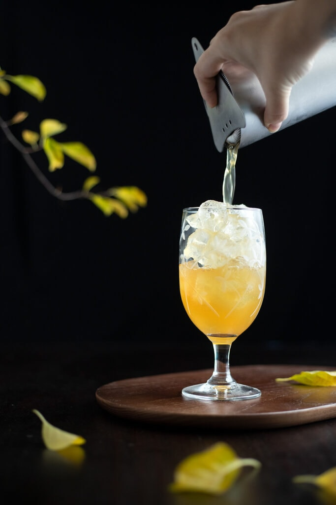 straining the cocktail into a glass filled with ice