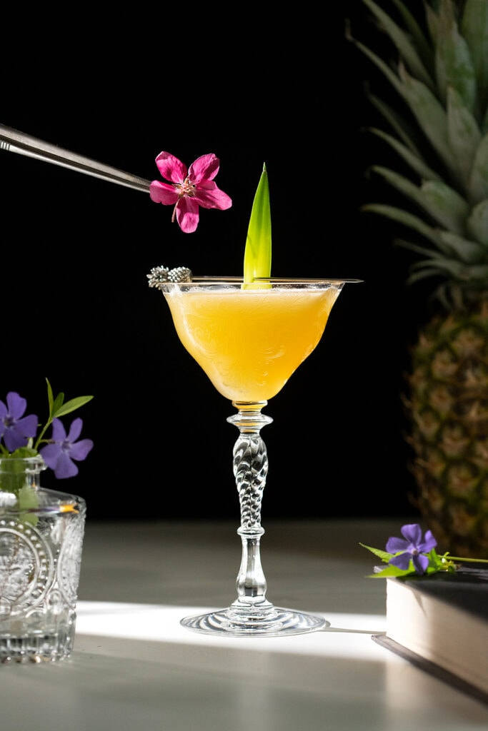 tongs holding an edible flower over a cocktail.
