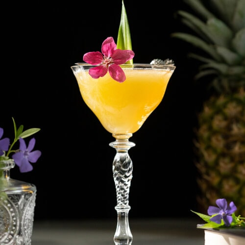 yellow cocktail with a flower and pineapple leaf