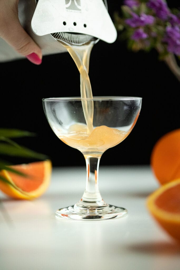 pouring the cocktail into a coupe glass.