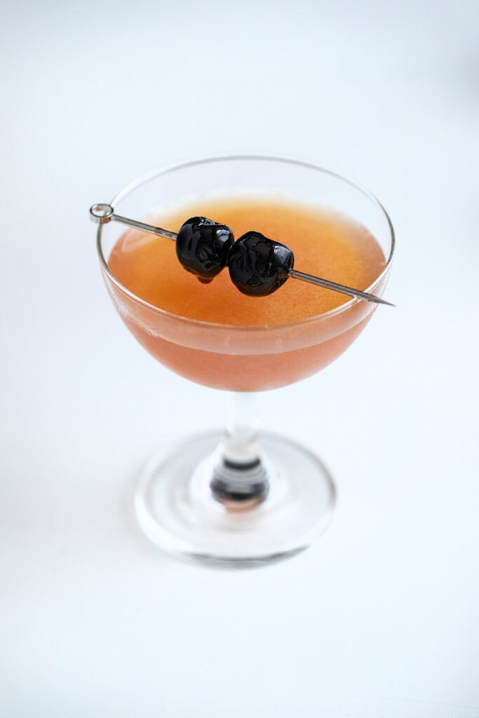 ward eight cocktail in a coupe glass with two cherries on a pick.