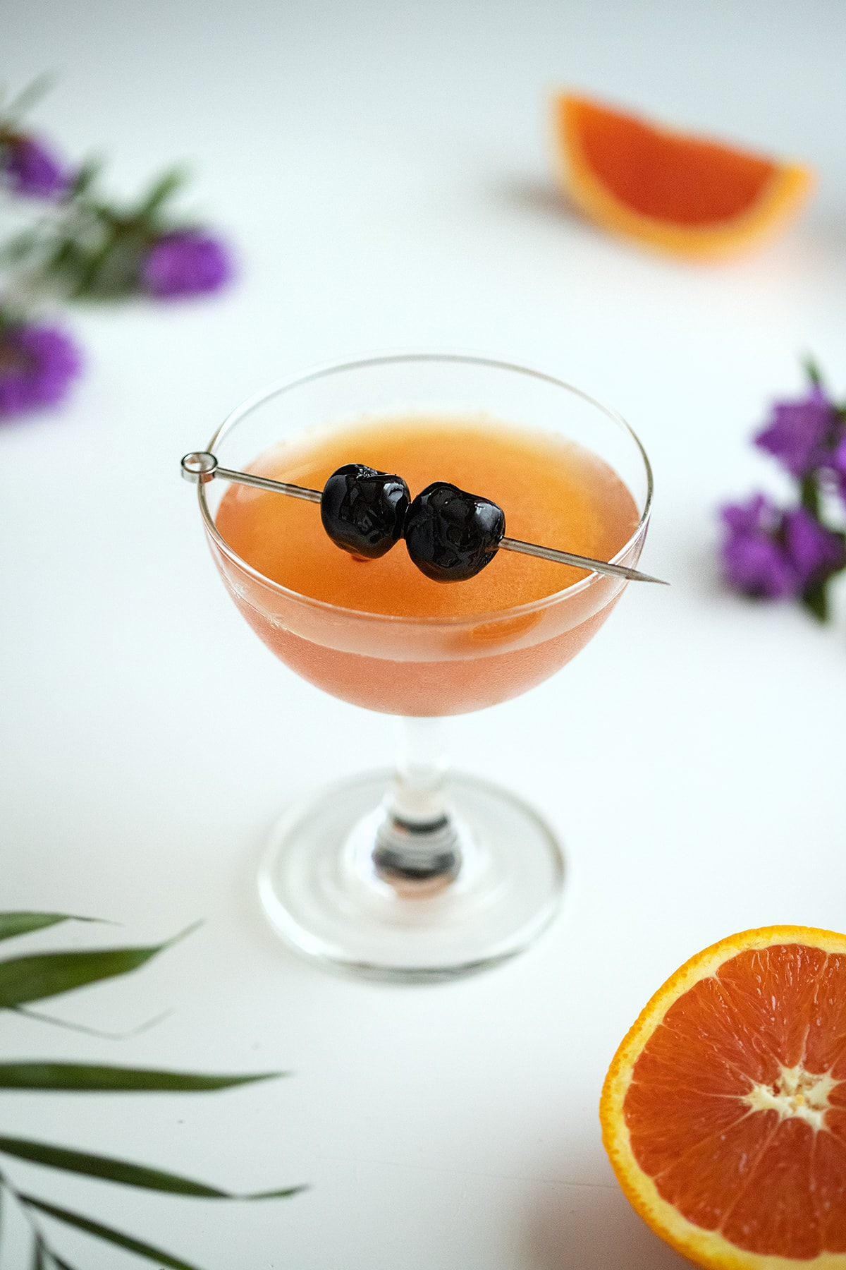 whiskey cocktail with two cherries in a coupe glass