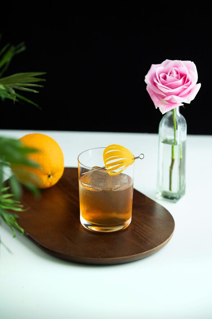 a drink on the rocks on a cutting board with an orange.