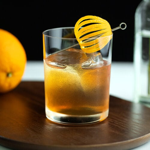 a whiskey cocktail in a rocks glass with a fancy orange peel.