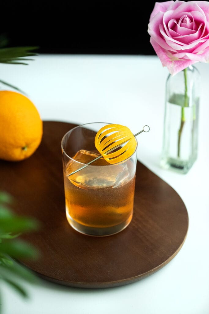 whiskey cocktail in a rocks glass with an orange peel on a pick.
