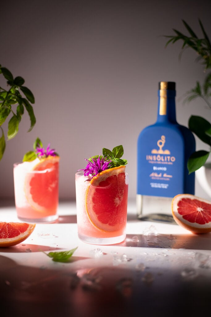two drinks with grapefruit slices next to a blue tequila bottle.